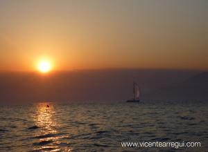 Algunos veleros se dirigen a la costa al caer el sol